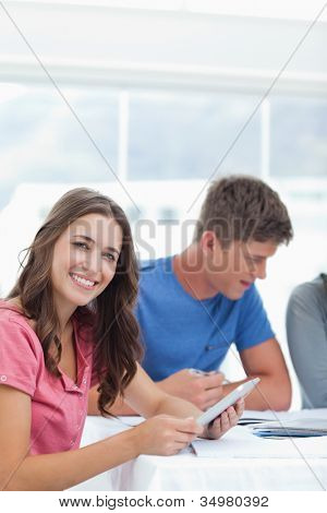 A girl uses her tablet pc and smiles as she sits beside her friends