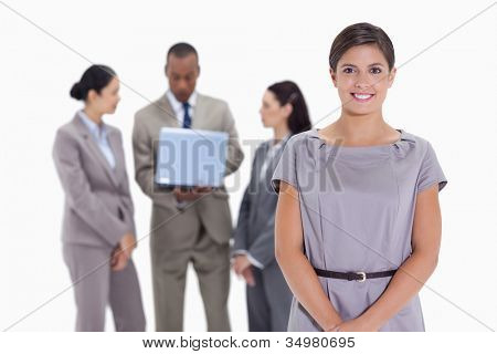 Close-up of a woman smiling with business team in the background with a laptop which a man is looking at the screen and the others are listening