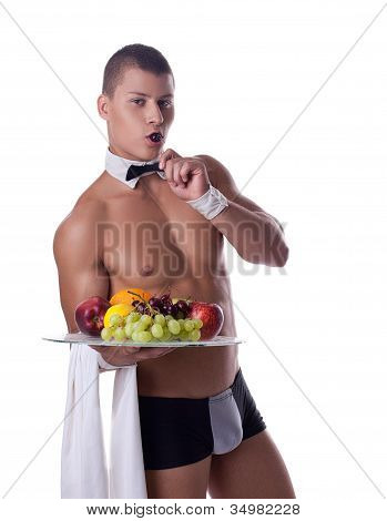 athletic man like striptease waiter hold fruits