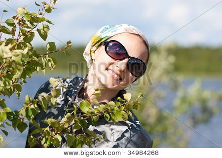 Portrait Of A Blond Girl Behind The Green Bush