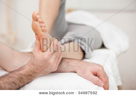 Woman having a foot massage while bending a leg in a medical room