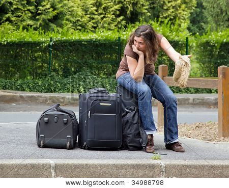 self hiker sitting on his luggage, complete discouragement