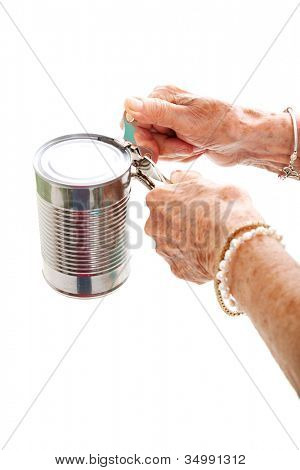 Closeup of elderly hands, with arthritis, struggling to use a can opener.  Isolated on white.