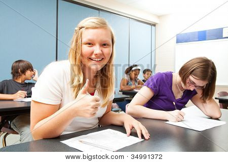 Pretty blond teen gives a thumbs up because she did well on a school test.