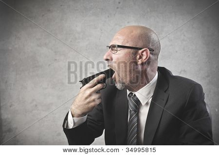 Businessman pointing a gun in his mouth