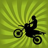 stock photo of dirt-bike  - Jumping Dirt Bike Silhouette on a Green Swirl Background - JPG