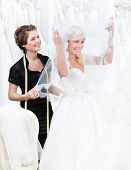 Постер, плакат: Магазин помощник помогает невеста надевать свадебное платье Невеста поднимает завесу