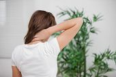 stock photo of herniated disc  - Brunette massaging her painful neck in a room - JPG