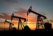 stock photo of oil rig  - Three pumps over orange sky  - JPG