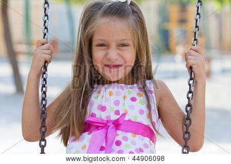 Little Girl Swinging In The Park