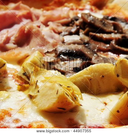 closeup of a four seasons pizza, with ham, artichokes, mushrooms and black olives