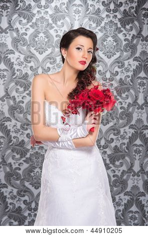 Young and beautiful bride standing with the flower bouquet over the grey background