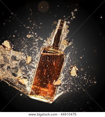 Isolated shot of whiskey splashing around bottler on black background