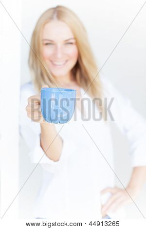 Blur image of cute blond girl hold blue cup of coffee on white background, morning drink, happiness concept