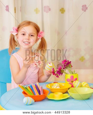 Sweet little girl paint Easter eggs on drawing lesson, having fun in daycare, traditional Christian holiday, joy and pleasure concept
