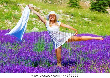 Attractive blond female wearing white summertime hat and dress dancing on lavender meadow, raised up hand holding shawl, having fun outdoors, vacation concept
