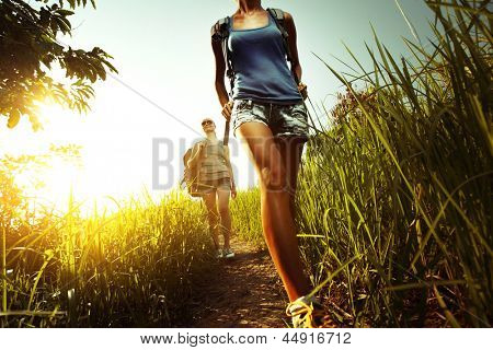 Two young ladies walking with backpacks on a thin path through a lush tropical meadow