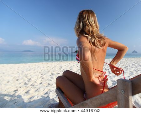Young lady relaxing in a chair on a white sand beach and untying her bra