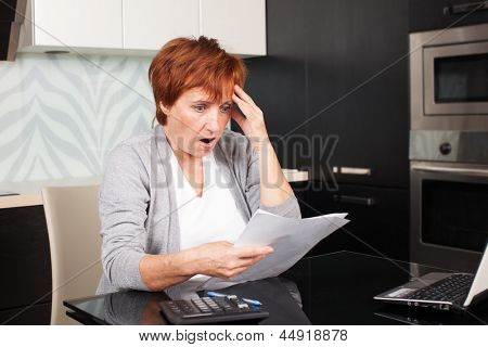 Elderly woman sorting through her old receipts at home. Sad businesswoman with document