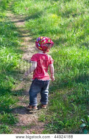 Little Cute Girl Is Walking On A Footpath
