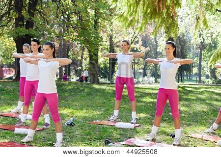 Group of sporty women doing exercise in city park