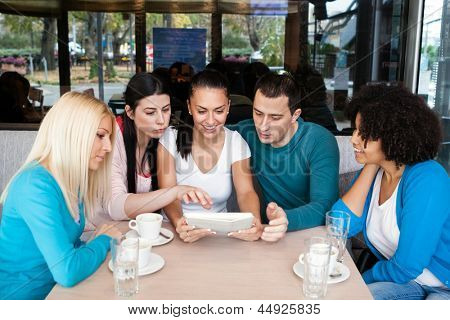 Group of teenagers in cafe having fun with tablet