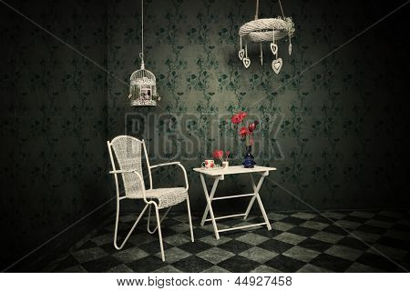 old room with floral wallpaper, tiled floor, chair and table, cup of tea vase with flowers and birdcage full of flowers
