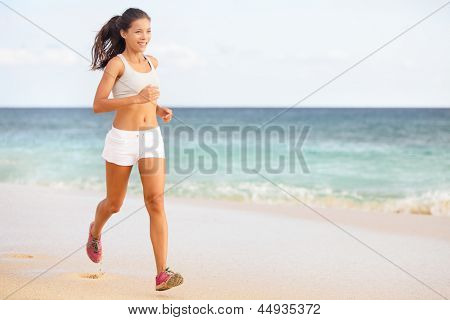 Woman runner jogging or running on beach training in barefoot sport shoes. Beautiful young fit fitness model in working out outside in summer wearing shorts. Mixed race Asian / Caucasian female girl