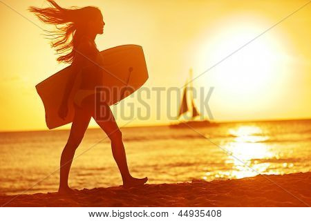 Summer woman body surfer beach fun at sunset. Body surfing girl walking in sunshine in warm evening sun with body surfboard. Water sport vacation travel concept. Kaanapali beach, Maui, Hawaii, USA