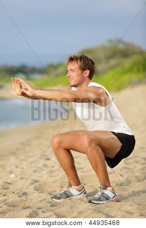Fitness man training air squat exercise on beach outside. Fit male exercising crossfit outside. Young handsome caucasian male fitness model and instructor outdoors