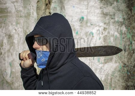 Man with a machete on shoulder on a wall background