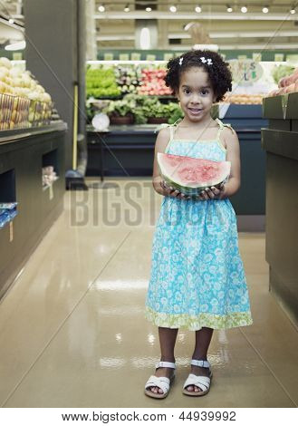Portrait of girl holding slice of watermelon in grocery store