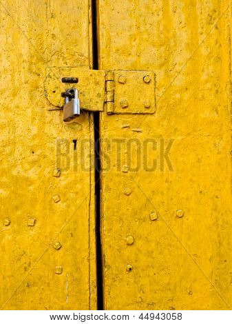 Padlock on an old yellow metallic door