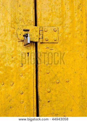 Padlock on an old yellow metallic door