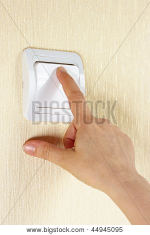 Mano enciende el lightswitch en la pared