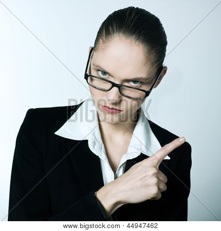 studio shot portrait of one beautiful business strict  nanny teacher woman pointing