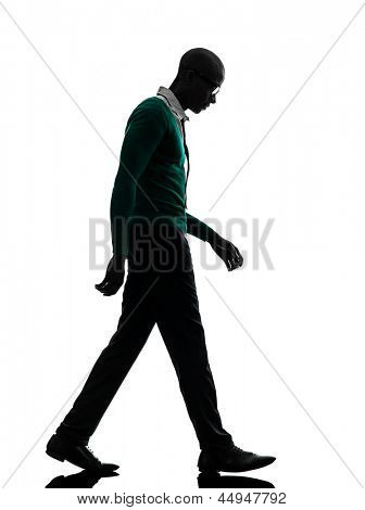 one african  black man walking looking down sad  in silhouette studio on white background