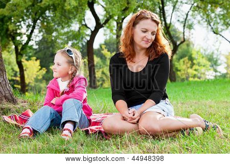 Sad Mother And Little Daughter Having A Quarrel, Looking In Different Directions