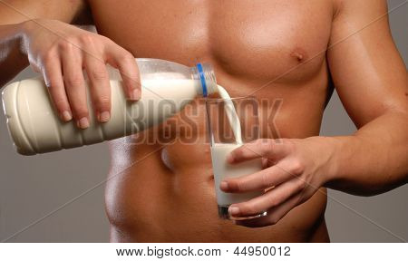 Shaped and healthy body man pouring milk glass.