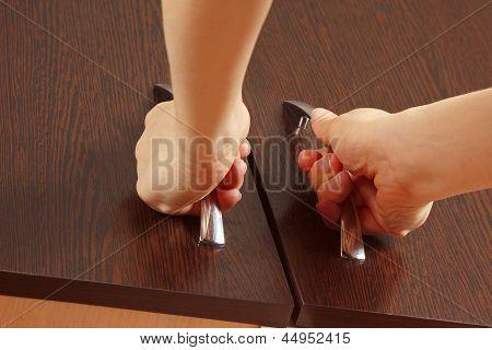 Women's hands closed cabinet doors