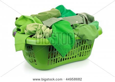Green clothes in a laundry basket on white background concept for environmental conservation and eco friendly washing