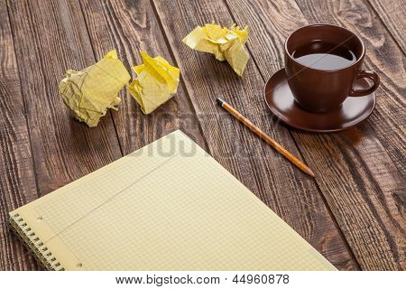 Notepad on a wooden table with crumpled sheets around
