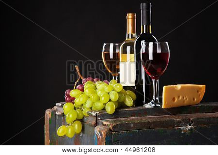Wine, grapes and cheese on black background