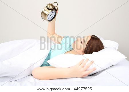 Beautiful young woman on bed with alarm clock in bedroom