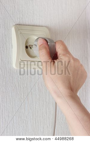 Hand inserting electric plug in socket on the wall