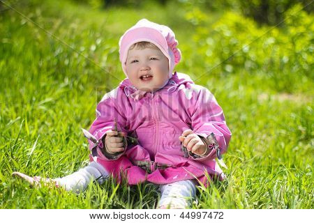 Portrait Of Funny Lovely Little Girl Sitting On A Green Grass