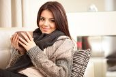 stock photo of sofa  - Happy young woman sitting on sofa in cosy cloths with cup of coffee - JPG