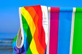 stock photo of nudism  - a swimsuit patterned with the rainbow flag on a deck chair of different colors on the beach - JPG