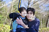 stock photo of wheelchair  - Little disabled boy in wheelchair hugging older brother outdoors smiling together - JPG