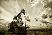 stock photo of pipeline  - Oil pump industrial machine for petroleum in the sunset background - JPG